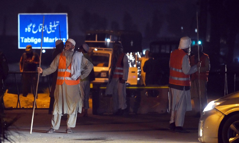 Volunteers stand guard near the site of a motorcycle bomb attack in Lahore. —AFP