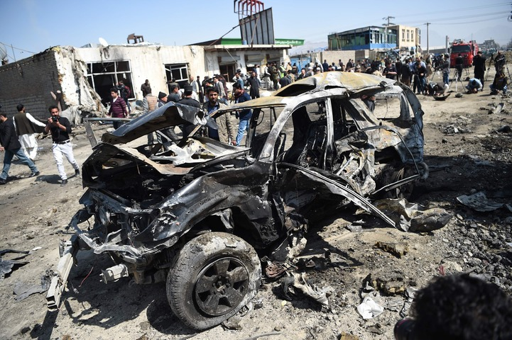 Afghan security personnel and civilians gather next to a damaged car at the site of a car bomb attack in Kabul on March 17, 2018. ─AFP