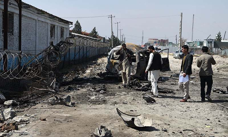 Afghan security personnel inspect the site of a car bomb attack in Kabul on March 17, 2018. — AFP