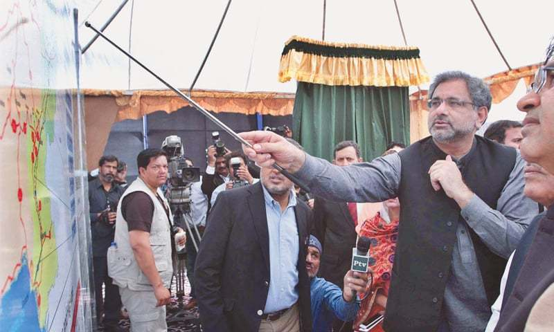 PRIME Minister Shahid Khaqan Abbasi points to a particular area of the newly-built Rai Mansab Ali Khan Kharal Bridge during a briefing on the project.—APP