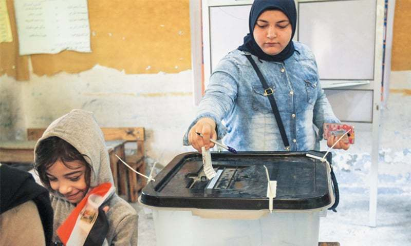 Woman carries sick husband to vote in Egypt's presidential election