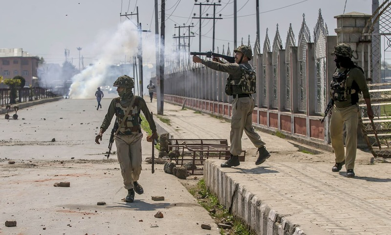 Indian paramilitary soldier fires tear gas shell towards Kashmiri protester during a protest in Srinagar. —AP