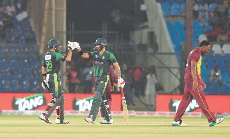 KARACHI: Pakistan's young batsmen Babar Azam (L) and Hussain Talat congratulate each other as they complete a 100-run partnership during the second Twenty20 International against the West Indies at the National Stadium on Monday.—Tahir Jamal/White Star