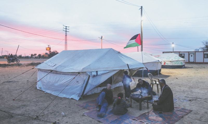 GAZA CITY: Palestinians prepare coffee outside their tents along the border with Israel during a protest in support of Palestinian refugees' right of return to lands they were expelled from during the 1948 war surrounding Israel's creation.—AFP