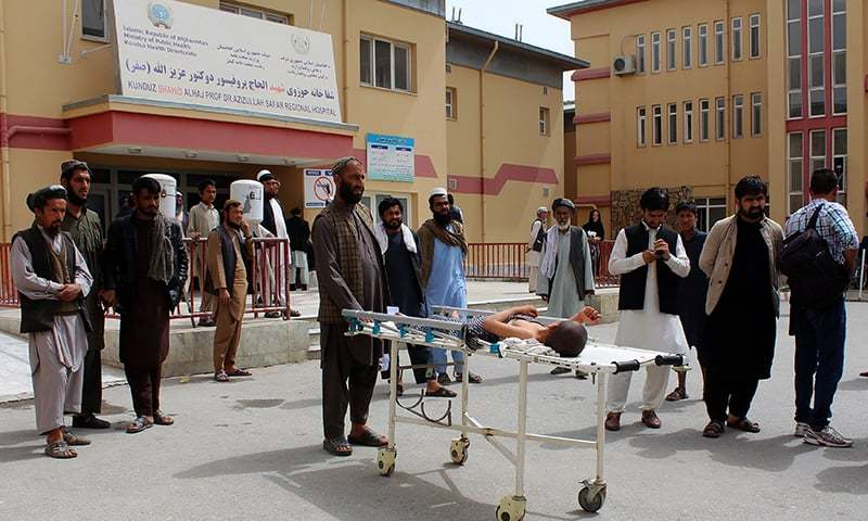 An injured Afghan boy lays on a stretcher outside a hospital in Kunduz, a day after an airstrike on a religious school. — AFP