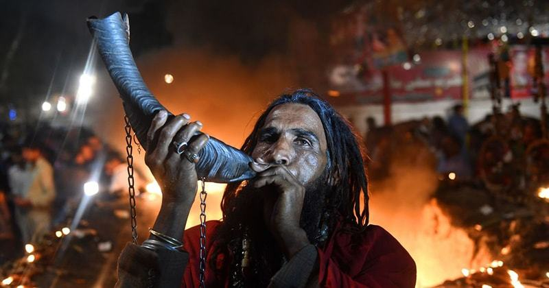 A devotee blows a horn at the shrine of Madho Lal Hussain during the three-day long Mela Chiraghan festival in Lahore on March 24, 2018.   Arif Ali/AFP