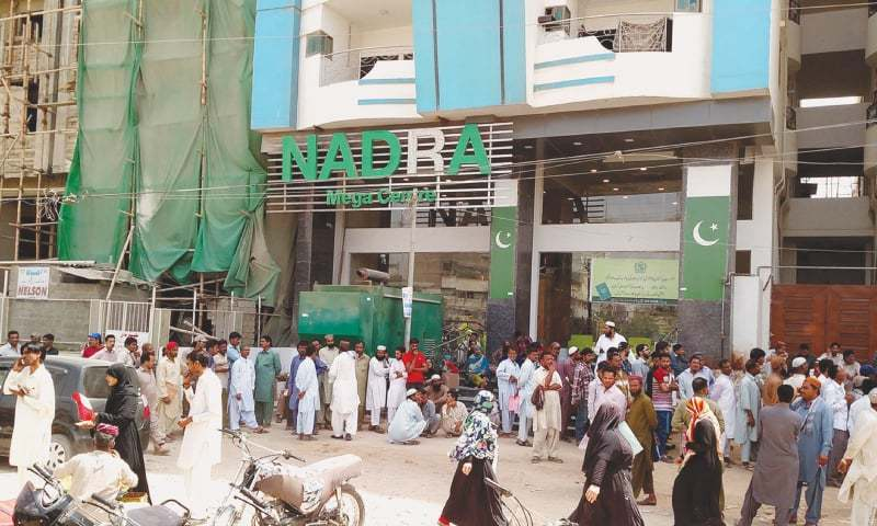 LONG queues are routine outside the North Nazimabad mega centre.—Photo by writer