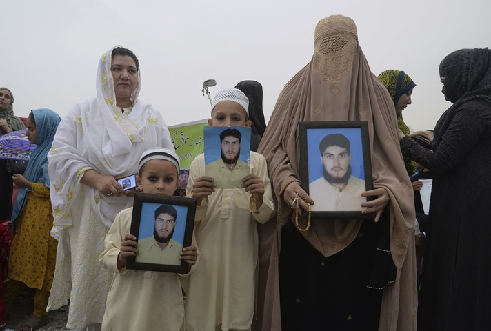 A family from a Pakistani tribal area display pictures of a missing family member during a rally in Peshawar on April 8, 2018. ─The Associated Press.