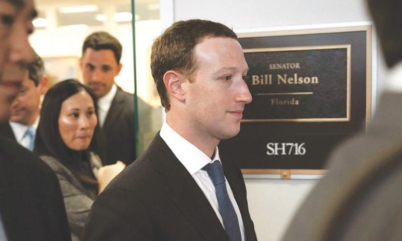 Washington: Facebook CEO Mark Zuckerberg (centre) leaves after a meeting with Senator Bill Nelson on Monday.—AFP