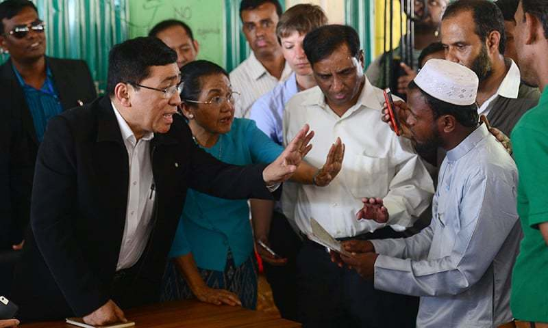 Myanmar Social Welfare Minister Win Myat Aye talks to Rohingya refugees during his visit to the Kutupalong refugee camp in Bangladesh. —AFP