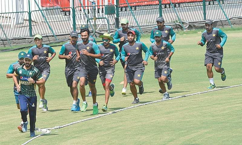PAKISTAN cricketers jog during a training session at the Gaddafi Stadium on Wednesday. —M.Arif/White Star