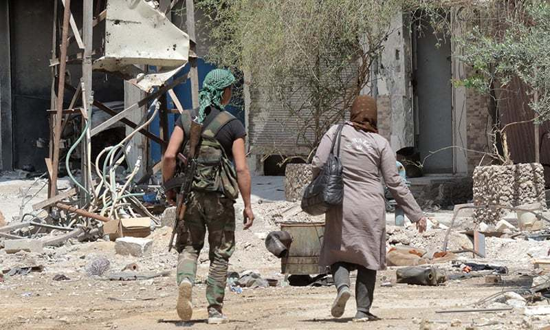 A Syrian soldier walks with a woman searching to find her home in a destroyed neighbourhood in the former rebel-held town of Zamalka in Eastern Ghouta. — AFP