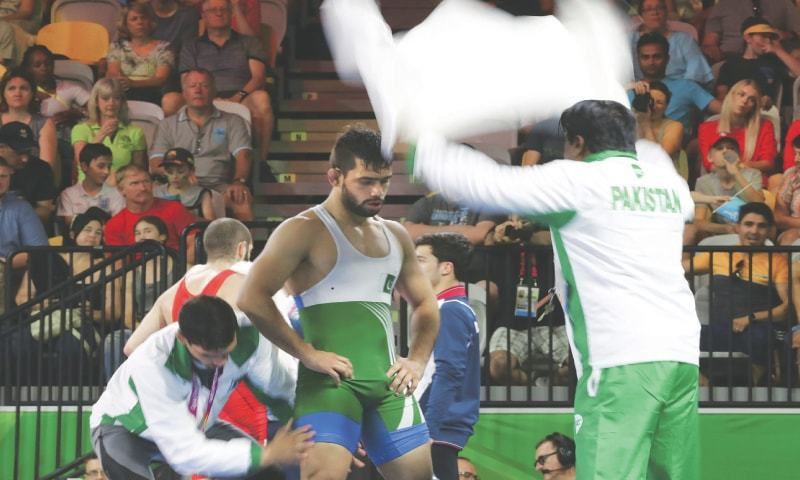 GOLD COAST: Pakistani wrestler Abdul Wahab is cooled down by his coach during the freestyle 65kg quarter-final against Adam Vella of Malta at the Commonwealth Games on Friday.—AP