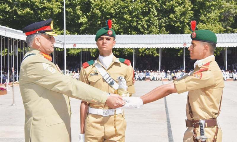 KAKUL: Chief of the Army Staff Gen Qamar Javed Bajwa awards the sword of honour to the best cadet of the 137th PMA Long Course during a passing-out parade on Saturday.—INP