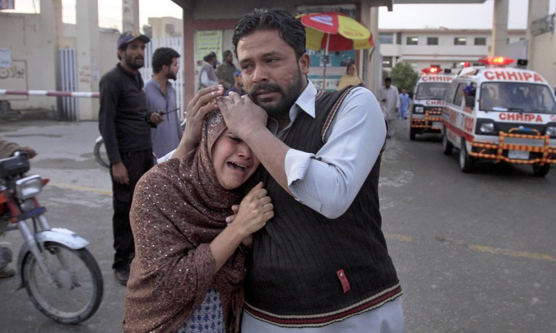 A man comforts a Christian woman who lost her husband in a deadly shooting incident in Quetta. —AP