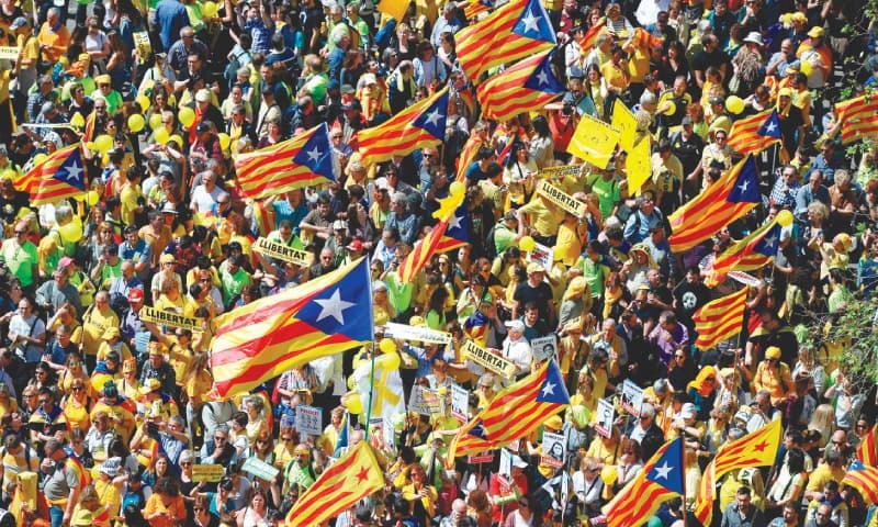 "BARCELONA: Protoesters wave Catalan pro-independence flags during a demonstration on Sunday to protest the jailing of nine Catalan separatist leaders facing trial on ""rebellion"" charges.—AFP"