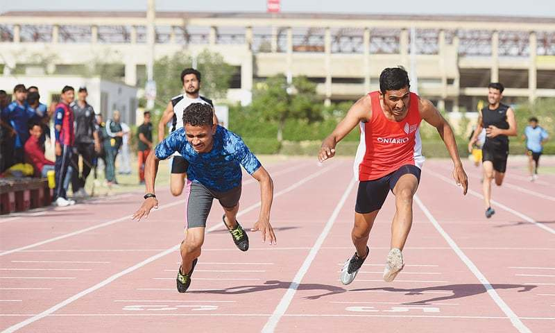 KARACHI: Athletes cross the finishing line in the men's 400m during the 17th Sindh Games at the PSB Coaching Centre on Friday. —Tahir Jamal/White Star