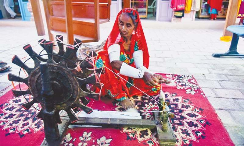 AN elderly woman makes thread by using a spinning wheel at a stall while traditional footwear are on display at another stall at the exhibition.—Fahim Siddiqi / White Star