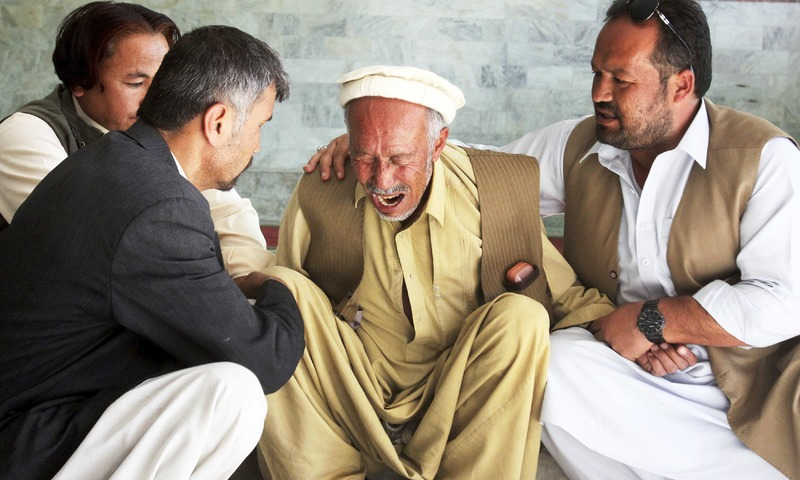 People comfort a man who lost his son in a deadly shooting incident in Quetta. —AP