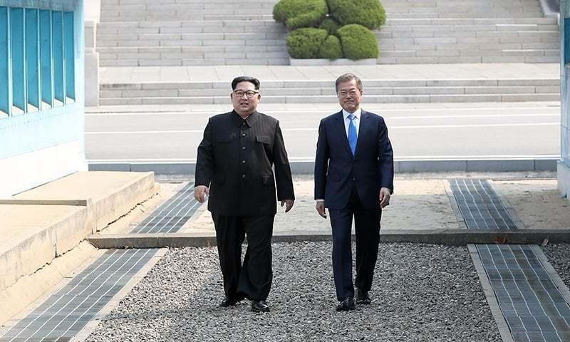 جنوبی کوریا کے صدر مون جے اِن (دائیں) اور شمالی کوریا کے لیڈر کِم جونگ اُن (بائیں) ڈیمارکیشن لائن پر جنوبی کوریا میں داخل ہوتے ہوئے — فوٹو، اے ایف پی