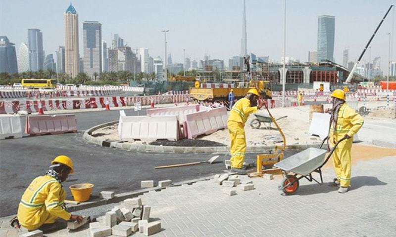Migrant labourers work on a road construction site in Dubai | AP
