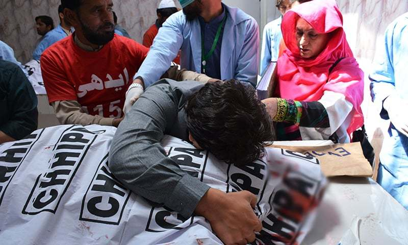 A man mourns the death of a relative at a hospital after assailants opened fire at an electronics shop in Quetta on Saturday. — AFP