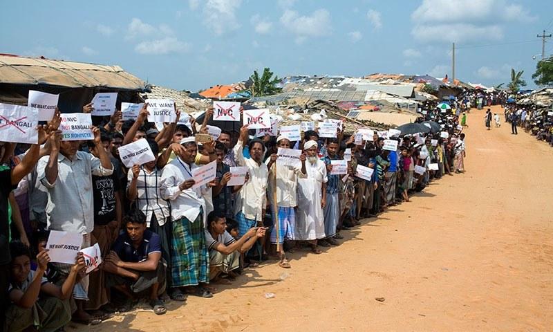 روہنگیا پناہ گزین اقوام متحدہ کی ٹیم کی آمد پر پلے کارڈز اٹھائے احتجاج کر رہے ہیں — فوٹو: اے پی