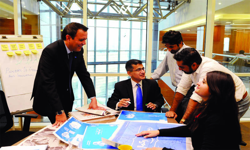 "Ali Habib, Head of Corporate Affairs & Marketing at UBL, assesses the response to his bank's <em>Rahbar-e-Taraqqi-o-Kamal</em> print campaign, with his team. UBL's print ads were published in Dawn to coincide with the 37 days between May and August 2017 when the newspaper's campaign, <em>The Dawn of Pakistan 1906-1948</em>, appeared. UBL's ads carried as baseline ""UBL celebrates Pakistan's 70th year of Independence with Dawn"" and showcased individuals, landmarks and icons that are intrinsically Pakistani. (photo: Arif Mahmood/ Dawn White Star)"