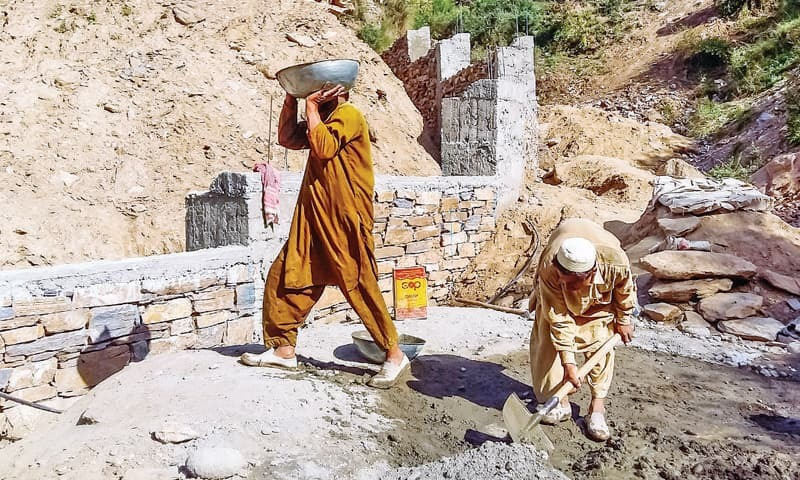 Ishaq and his uncle Ibrahim toil under blazing sun at a construction site in Kohistan Gut, Saidu Sharif. — Dawn