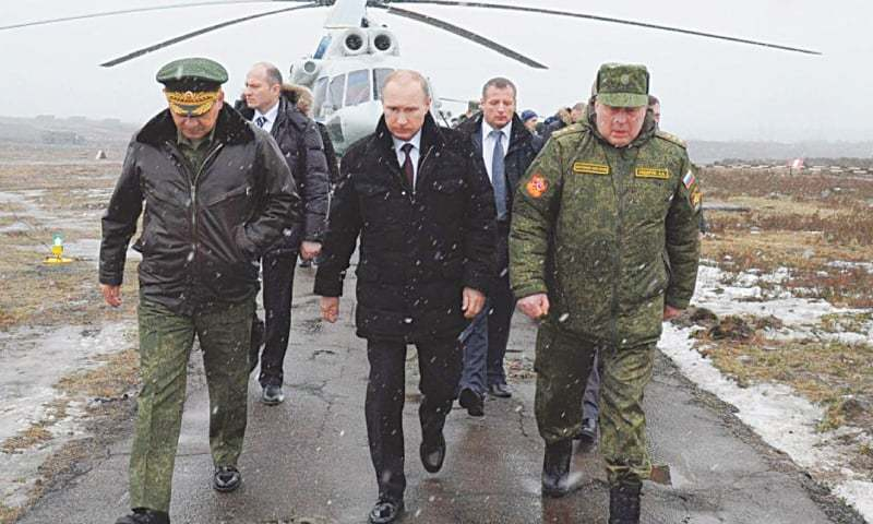 RUSSIAN President Vladimir Putin (centre) arrives to watch military exercises at the Kirillovsky firing ground in the Leningrad region in this file picture taken on March 3, 2014.—AFP