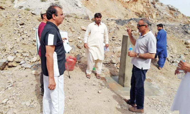 CDA team hold a discussion after fixing a pillar west of Nicholson Monument near Rawalpindi-Peshawar section of G.T. Road and Margalla Pass to demarcate the federal capital's boundary. — Photo by the writer