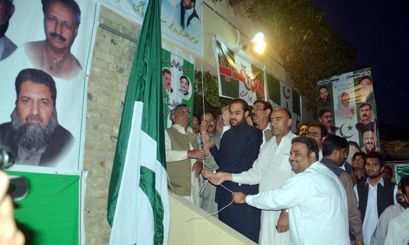 Former Balochistan chief minister Mir Abdul Quddus Bizenjo hoists a party flag during a ceremony on Sunday.—PPI