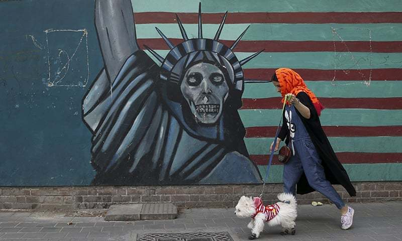 A woman walks her dog past an anti-US mural painted on the wall of the former US Embassy in Tehran, Iran. —AP