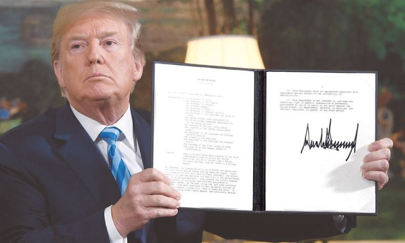 PRESIDENT Trump shows a document which he signed to pull US out of the Iran deal, which put curbs on Tehran's nuclear programme in return for lifting of sanctions.—AFP
