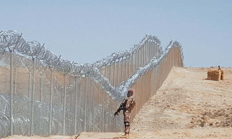 AN army soldier stands guard along the newly fenced part of the Pak-Afghan border after Chief of the Army Staff  Gen Qamar Javed Bajwa inaugurated the fencing work near the Panjpai area of Balochistan on Tuesday.—AFP