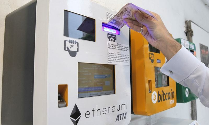 HONG KONG: A man uses the Ethereum ATM on Friday. Ethereum is one of the world's popular virtual currencies.—AP
