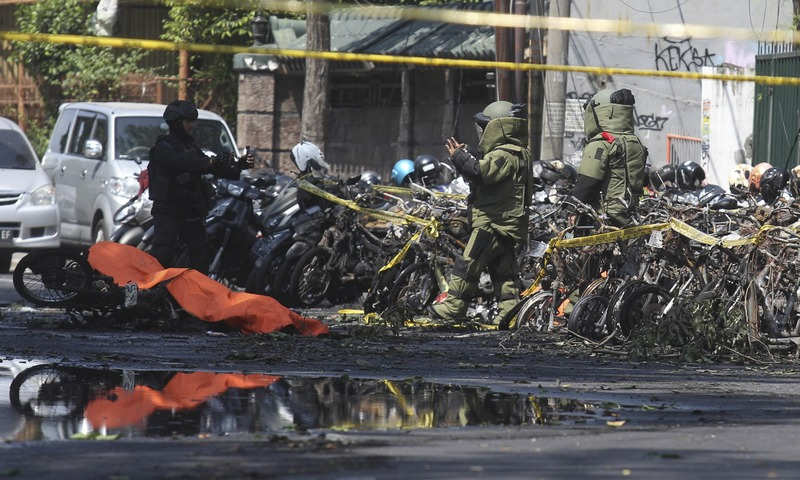 Members of police bomb squad inspect the wreckage of motorcycles at the site where an explosion went off outside a church in Surabaya, East Java, Indonesia. — AP