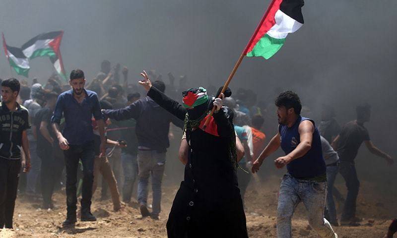 A Palestinian woman waves her national flag during clashes with Israeli forces near the border between Israel and the Gaza Strip, east of Jabalia on Monday, as Palestinians protest over the inauguration of the US embassy following its controversial move to Jerusalem. — AFP