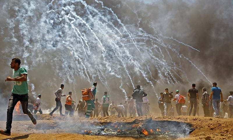 Palestinians run for cover from tear gas during clashes with Israeli security forces near the border between Israel and the Gaza Strip, east of Jabalia. — AFP