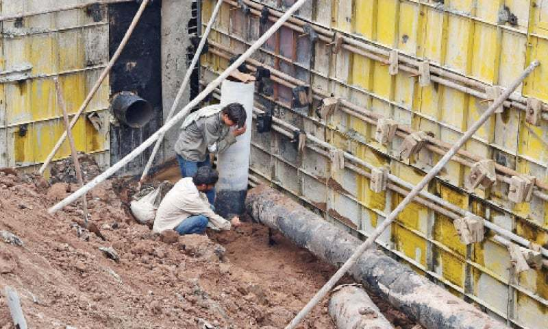 SNGPL workers repair a gas pipeline damaged during construction work on BRT project on GT Road, Peshawar, on Monday. — Photo by Abdul Majeed Goraya