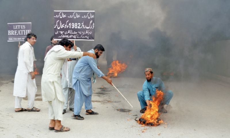 Protesters burn tyres during a rally by chemists in Peshawar on Tuesday against amended drug rules. — Photo by Shahbaz Butt