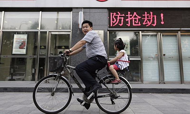 A man cycles past the headquarters of Industrial and Commercial Bank of China (ICBC) Ltd in Beijing. The bank opened a branch in Karachi in 2011, but has recently ramped up its efforts to denominate bilateral trade and investment transactions between China and Pakistan in the yuan.