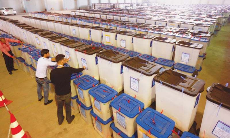 NAJAF: Employees of the Iraqi Independent High Electoral Commission inspect ballot boxes at a warehouse on Tuesday.—Reuters