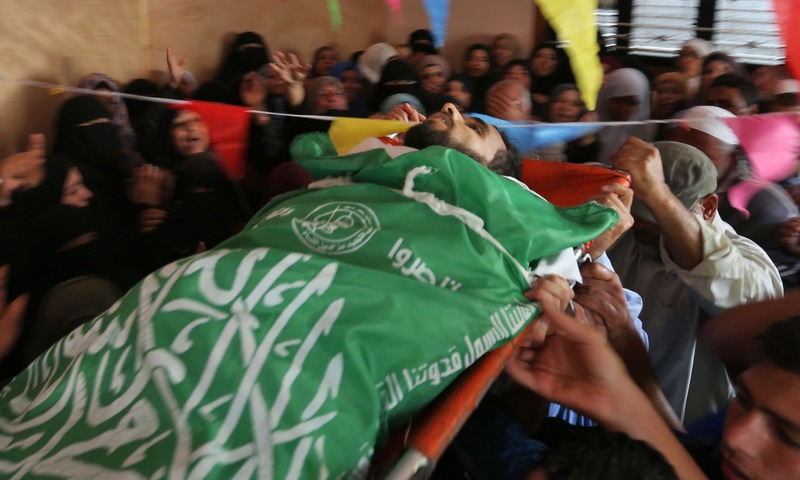Mourners carry the body of Mohammed Dwedar a 27-year old Palestinian, killed during clashes along the Gaza border. — AFP