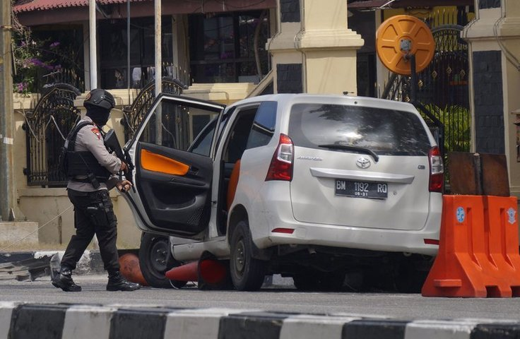 An officer inspects a minivan used in the attack at the regional police headquarters in Pekanbaru, Riau province, Indonesia, on Wednesday. — AP