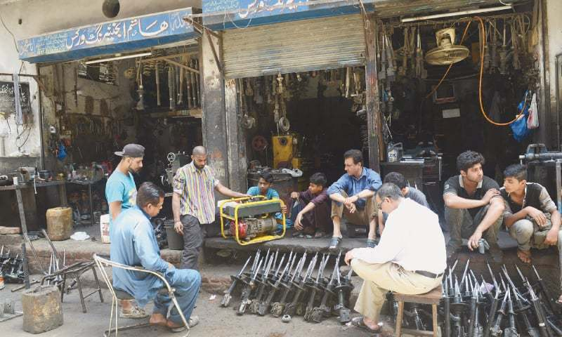 An electrician sits idle at his shop, unable to fix a generator during a power cut in Lahore.—Murtaza Ali/White Star