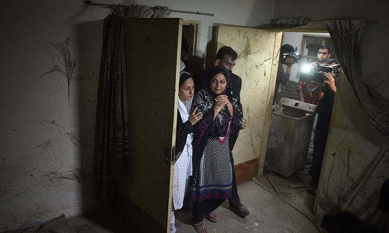 Asma Nawab (C) reacts as she enters her house in Karachi. —AFP