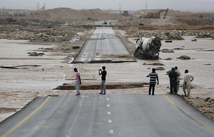 People visit a road which has been cut by the flood water after Cyclone Merkunu in Salalah Oman Saturday