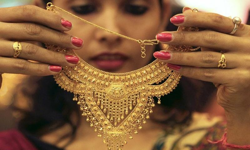 In this file photo, a salesgirl shows a gold necklace to customers at a jewellery showroom in the northern Indian city of Chandigarh.—Reuters