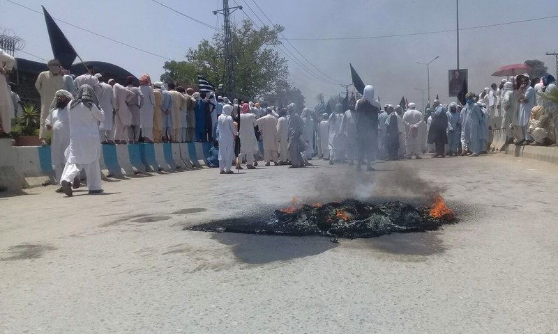 Trash and tires burning on the road leading up to the assembly. — DawnNewsTV